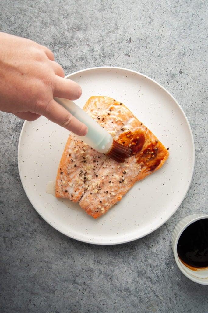 brushing teriyaki glaze on cooked salmon