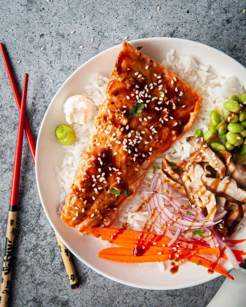 bowl of rice with teriyaki salmon, edamame, shiitake mushrooms, red onion, carrot, cream cheese, and wasabi
