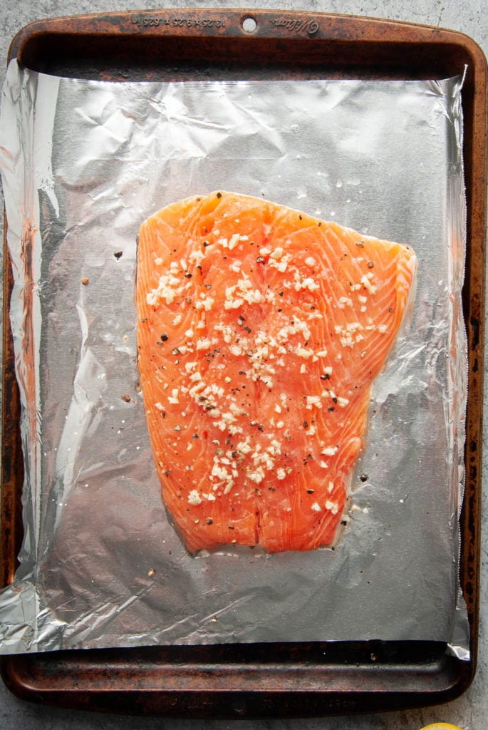 raw salmon on a baking sheet with tin foil with seasoning and garlic on top