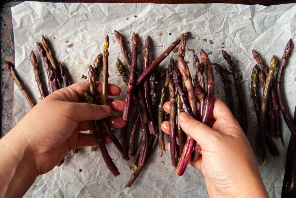 using hands to toss asparagus in olive oil