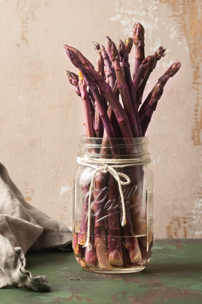 storing raw purple asparagus in a mason jar with water
