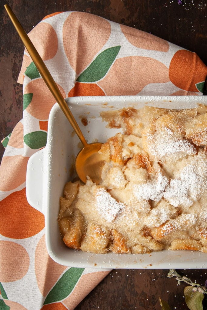 bread pudding in a casserole dish with gold serving spoon