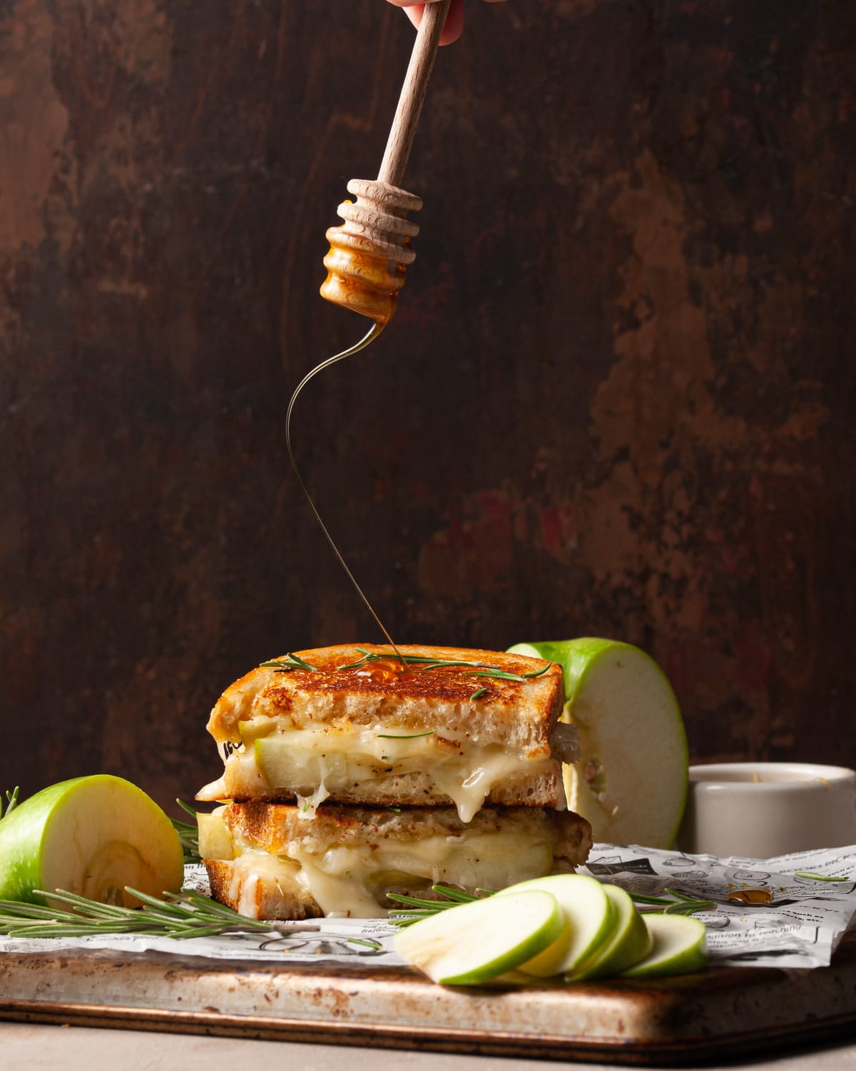 dripping honey over top a grilled cheese sandwich