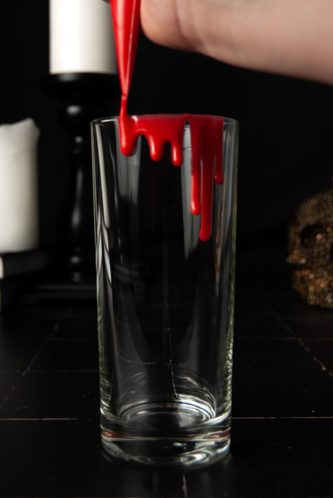 piping fake edible blood onto rim of cocktail glass
