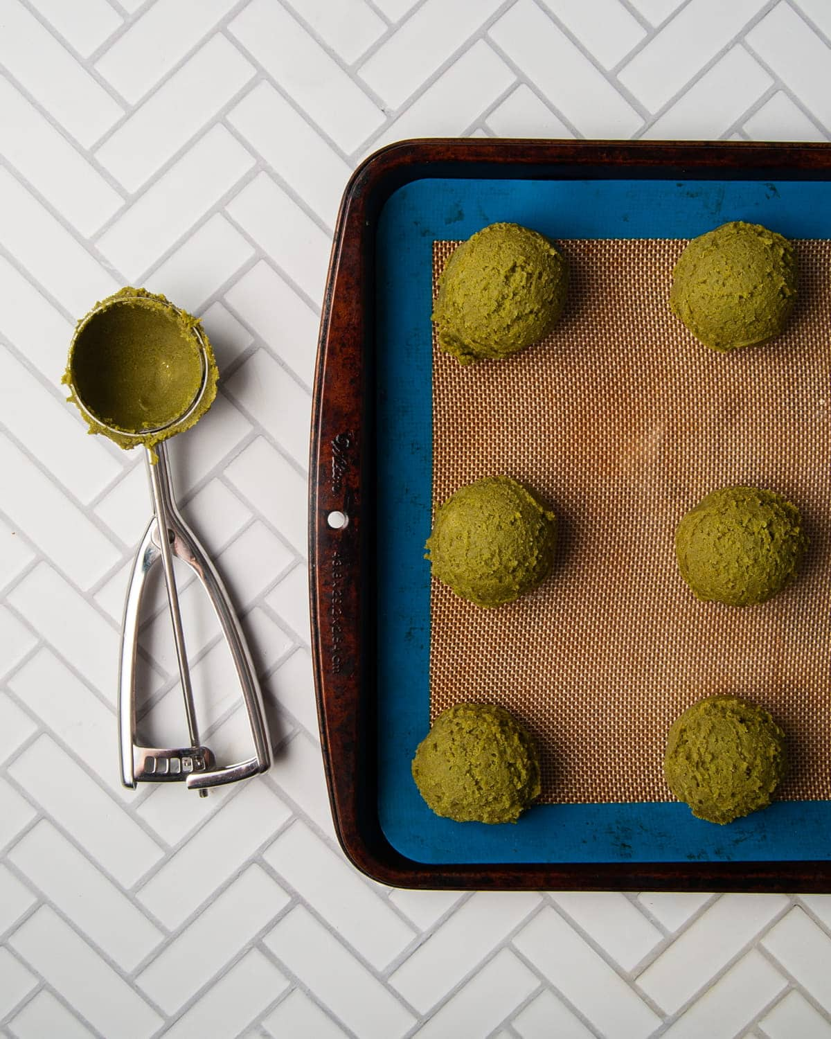using a cookie scoop to shape matcha cookies and place them on baking sheet
