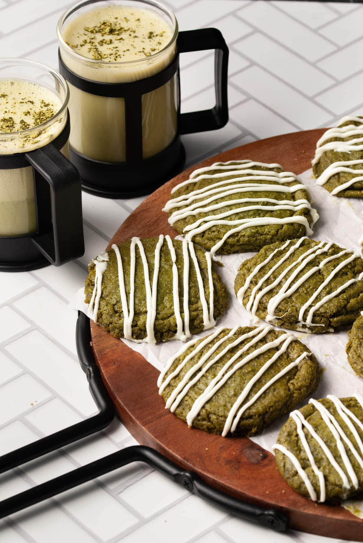 cropped picture of matcha cookies on a round wood board with two matcha lattes in the background