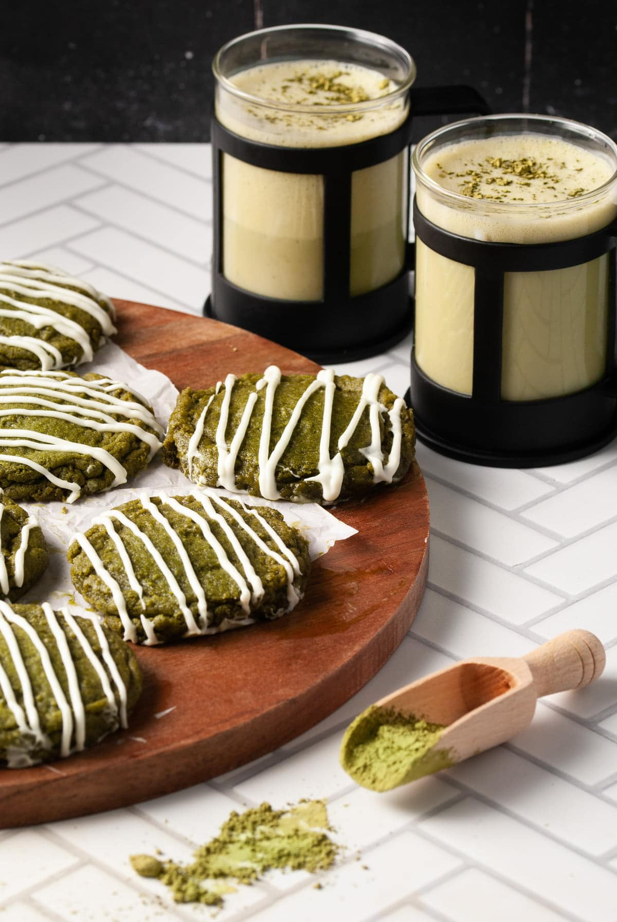 green cookies with white chocolate drizzle with two green lattes behing it