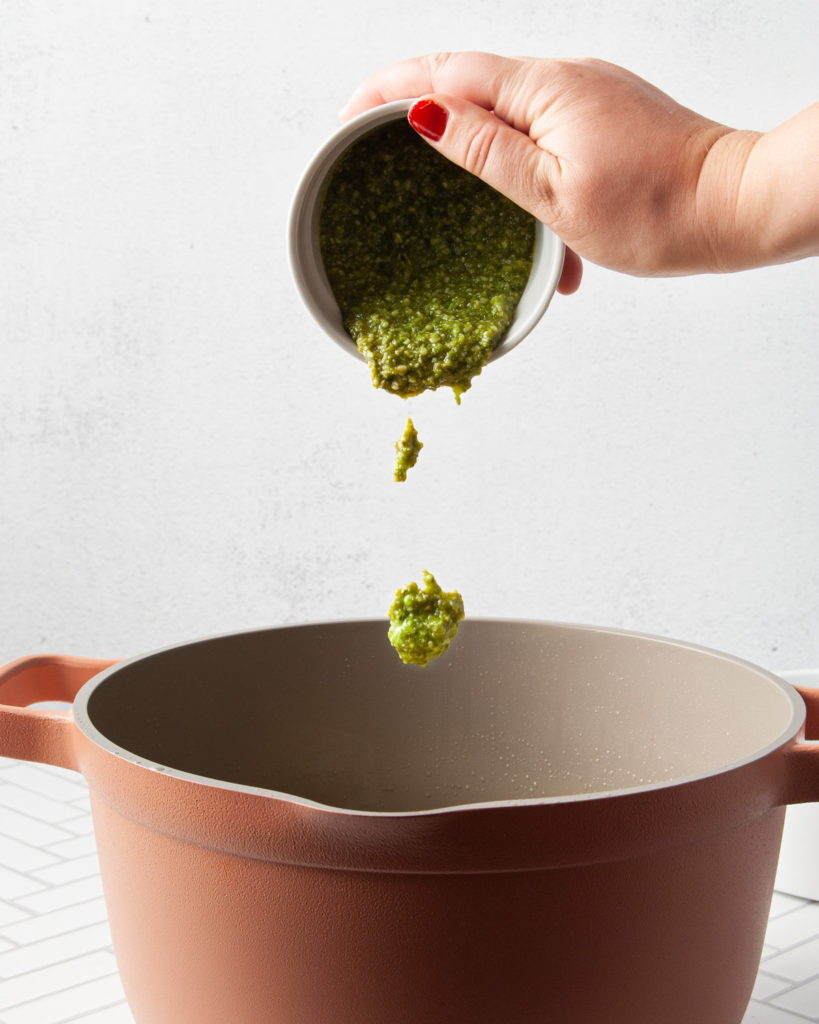 adding pesto to a large pot