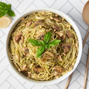 overhead shot of serving bowl filled with mushroom pesto pasta