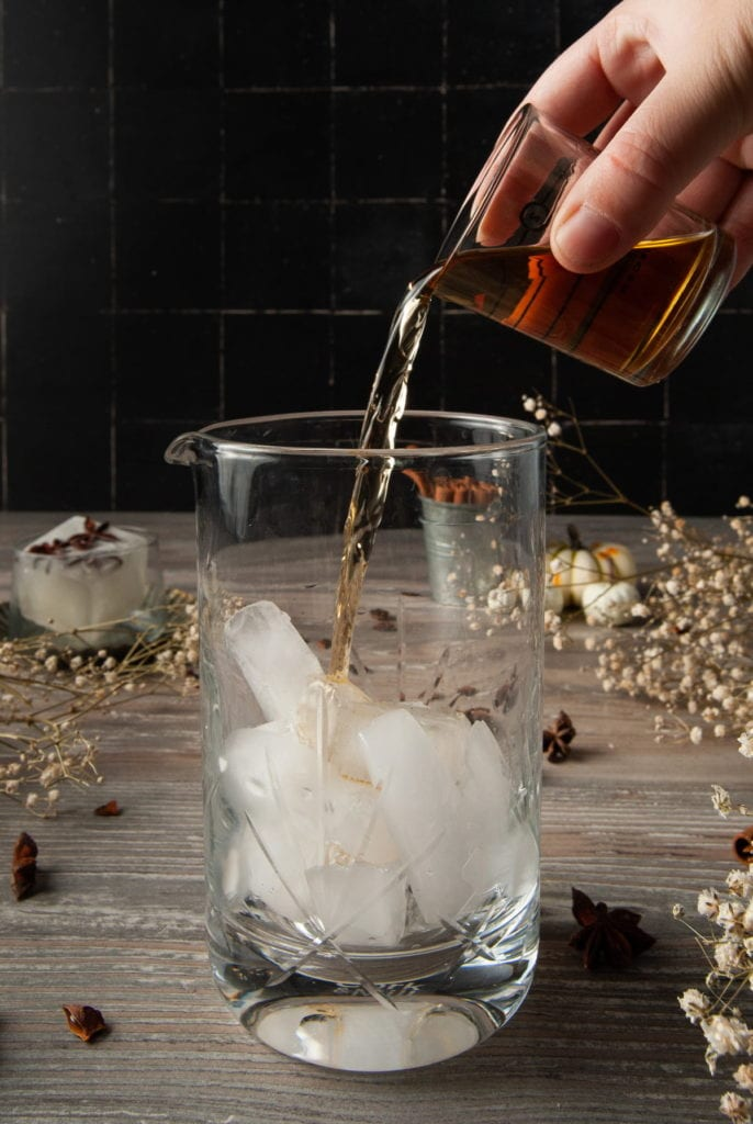 adding whiskey to a cocktail mixing glass