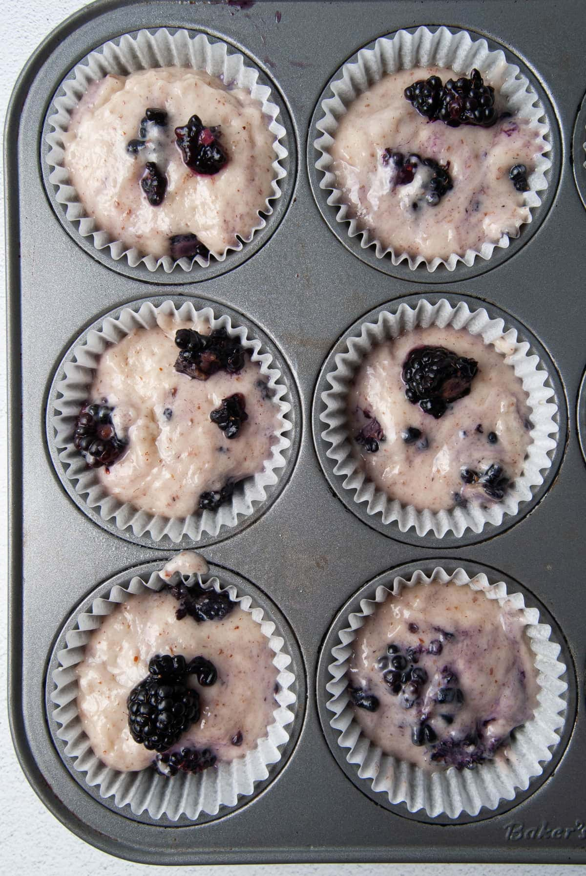Filling Muffin Tins with muffin batter and adding blackberries on top