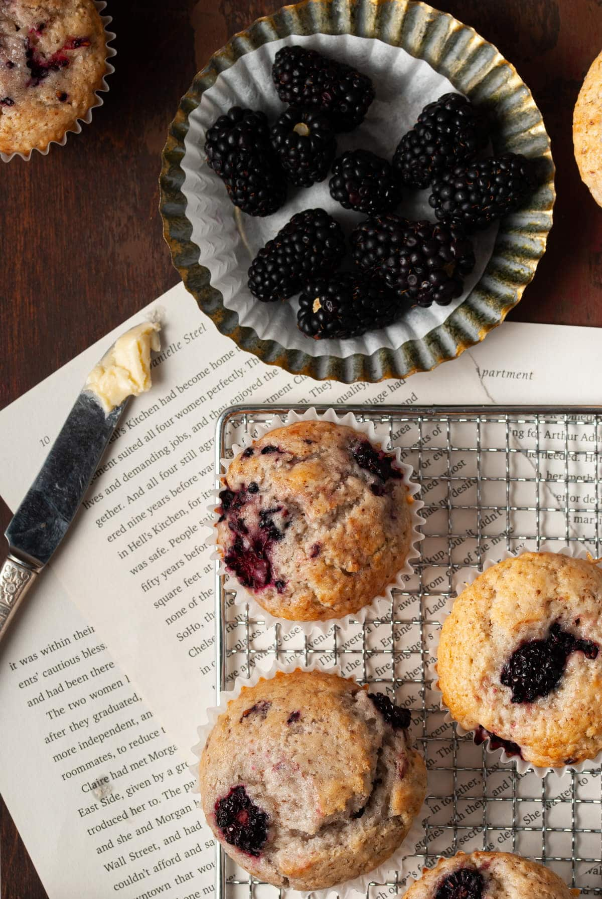 close up shot of fluffy muffins and a bowl of blackberries