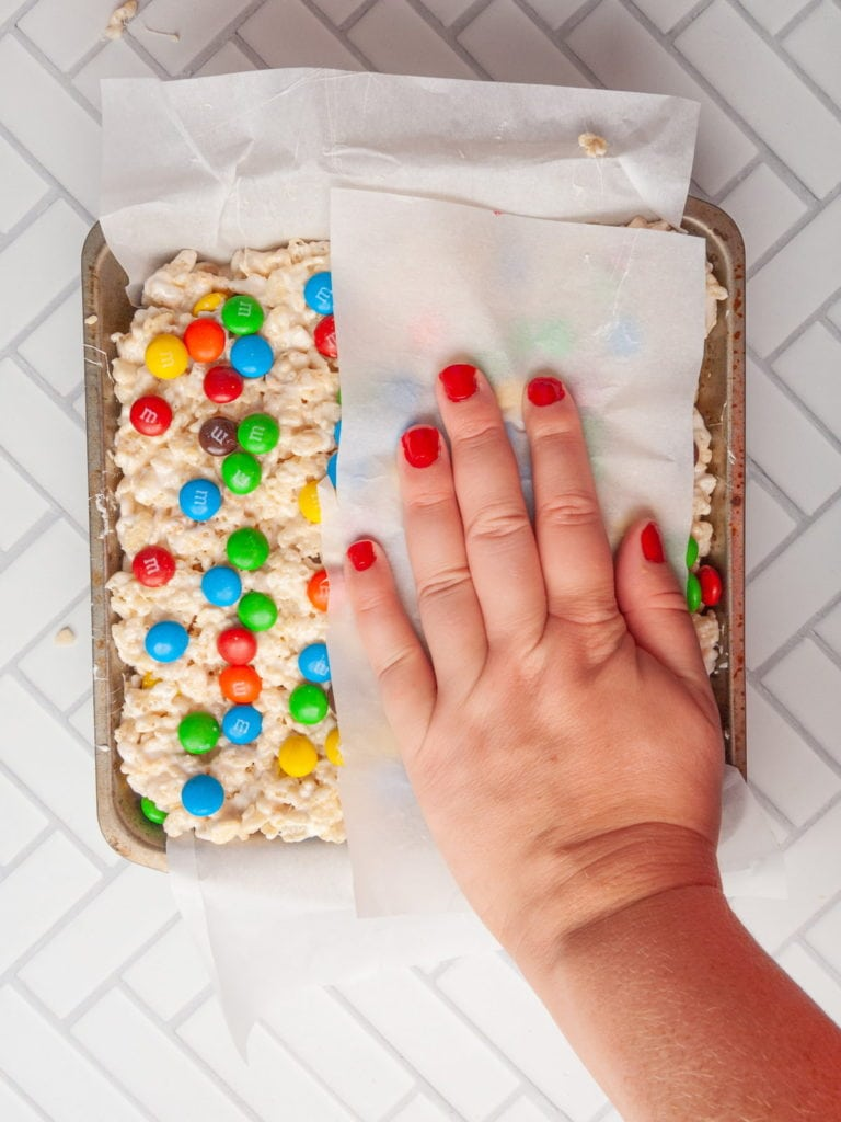 using your hand and parchment paper to push down rice krispie treats to set