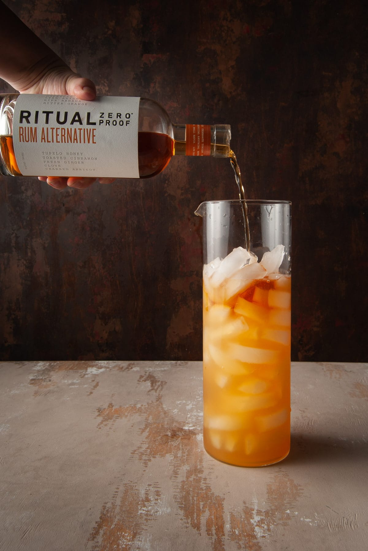 adding ritual rum alternative to a pitcher with ice and apple cider