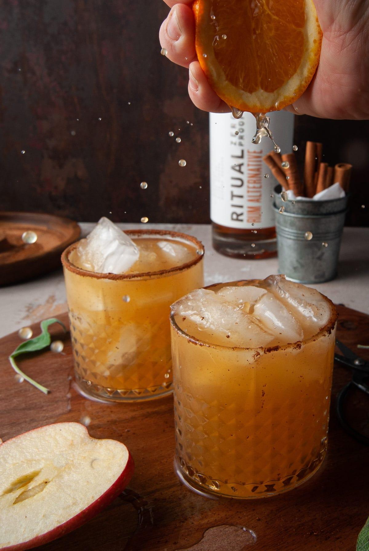 squeezing fresh orange juice into mocktail