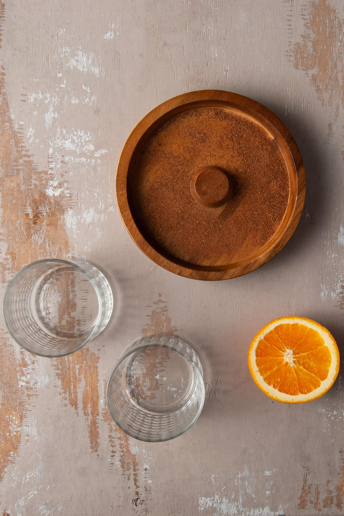 cocktail timmer filler with cinnamon, 2 glasses, and half an orange