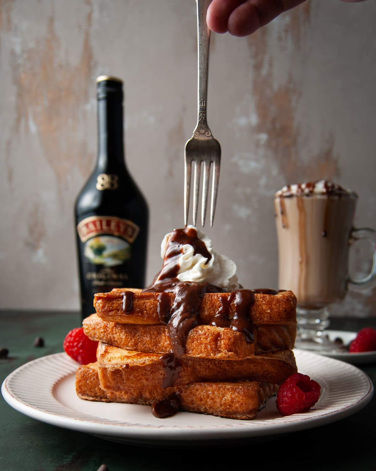 taking a fork to a stack of French Toast covered in chocolate