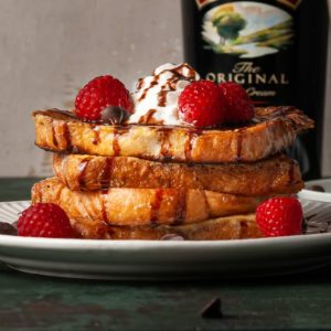 stack of french toast with whipped cream, chocolate syrup, and raspberries