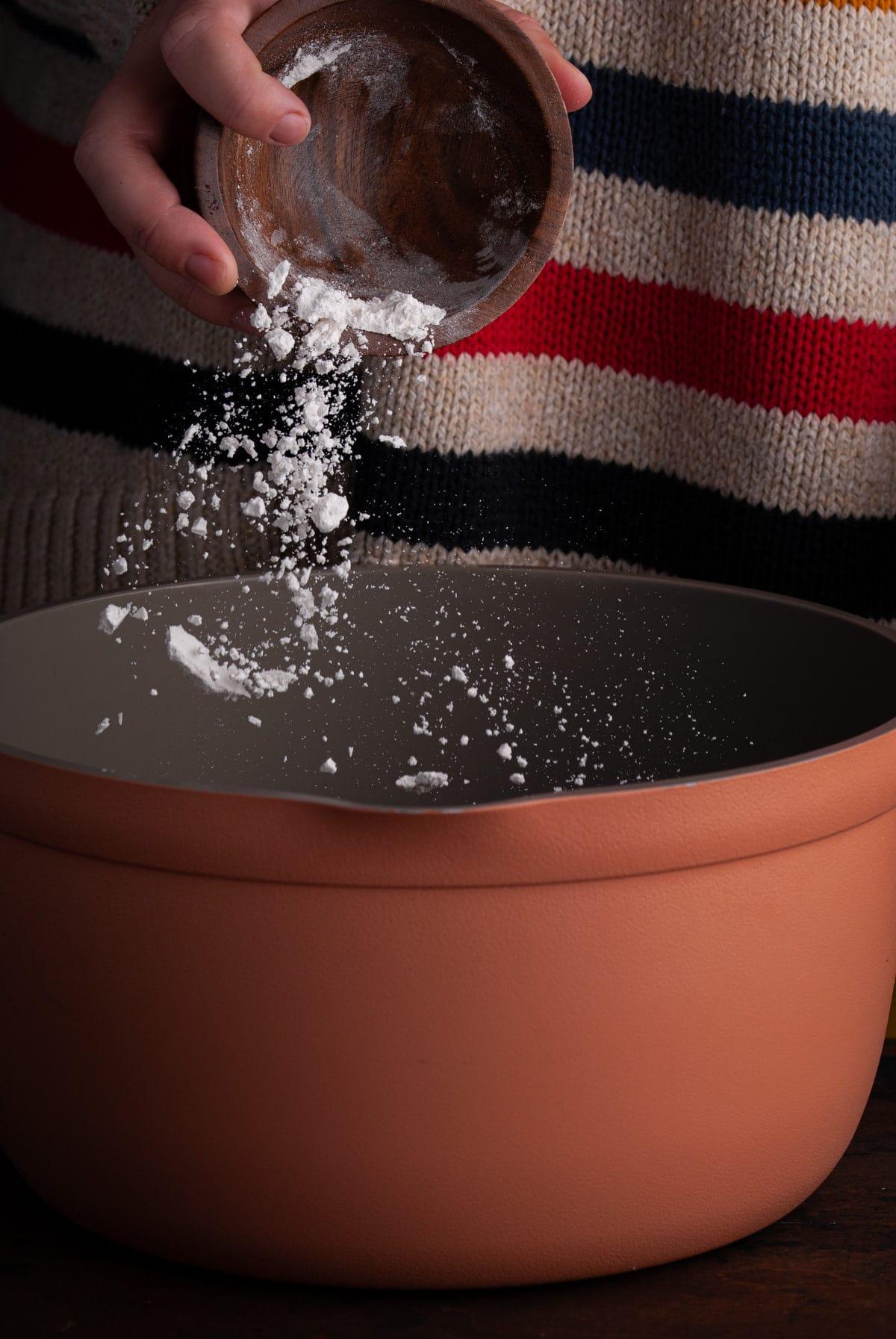 adding flour to a pot to make a roux