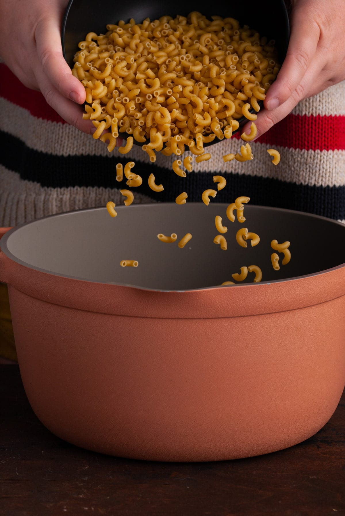 pouring macaroni into a big pot of boiling water