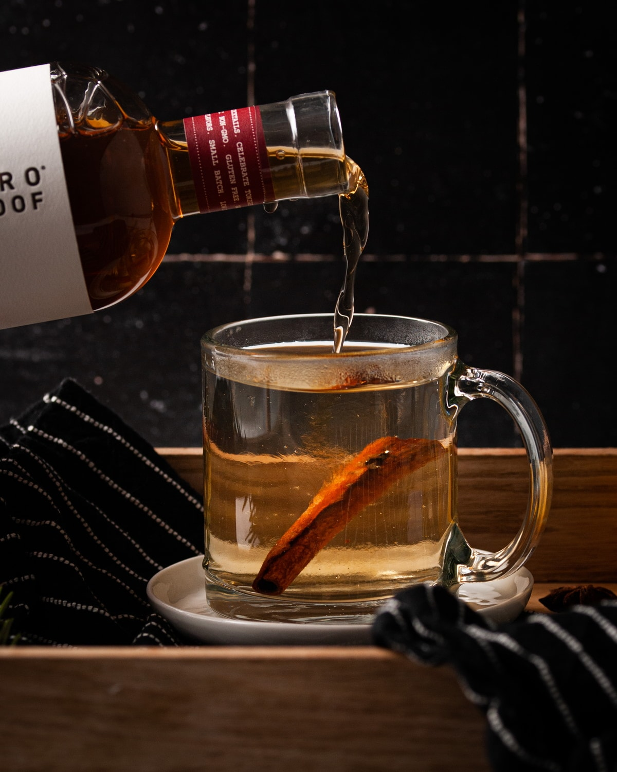 adding whiskey alternative to hot water and cinnamon stick