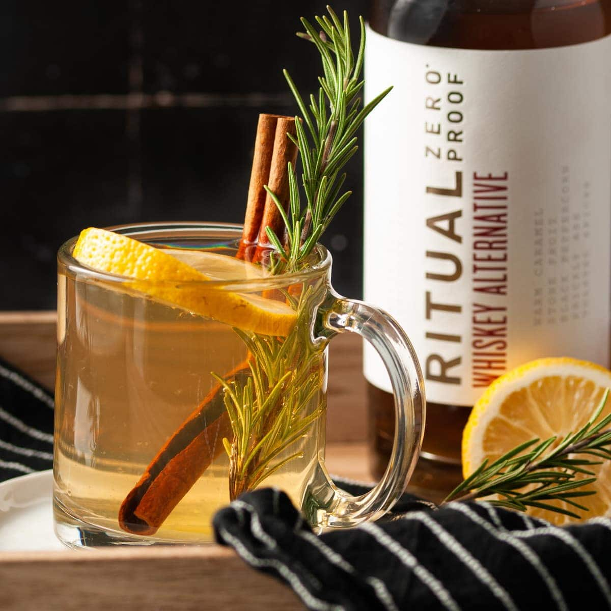 closeup of non-alcocolic hot toddy on a tray with ritual bottle behind it