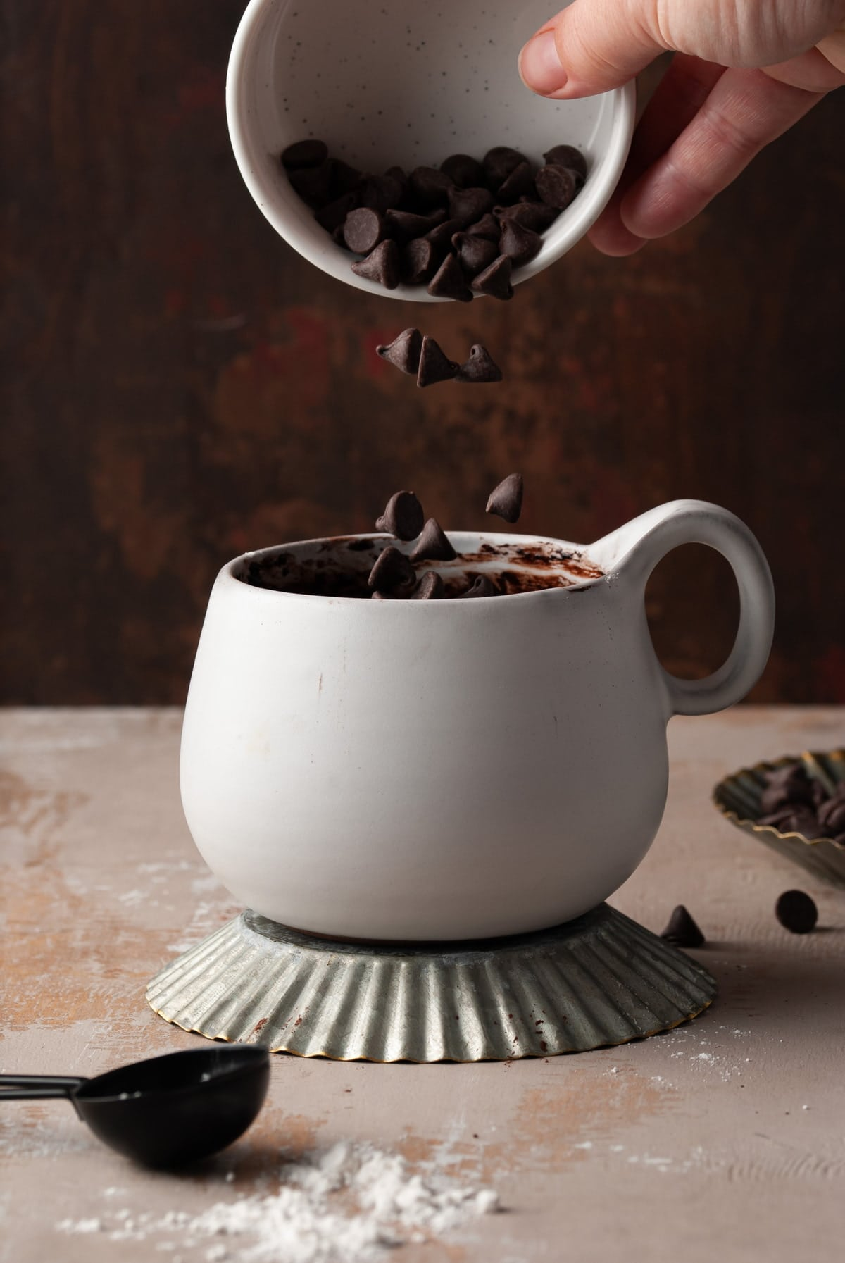 pouring chocolate chips into white mug