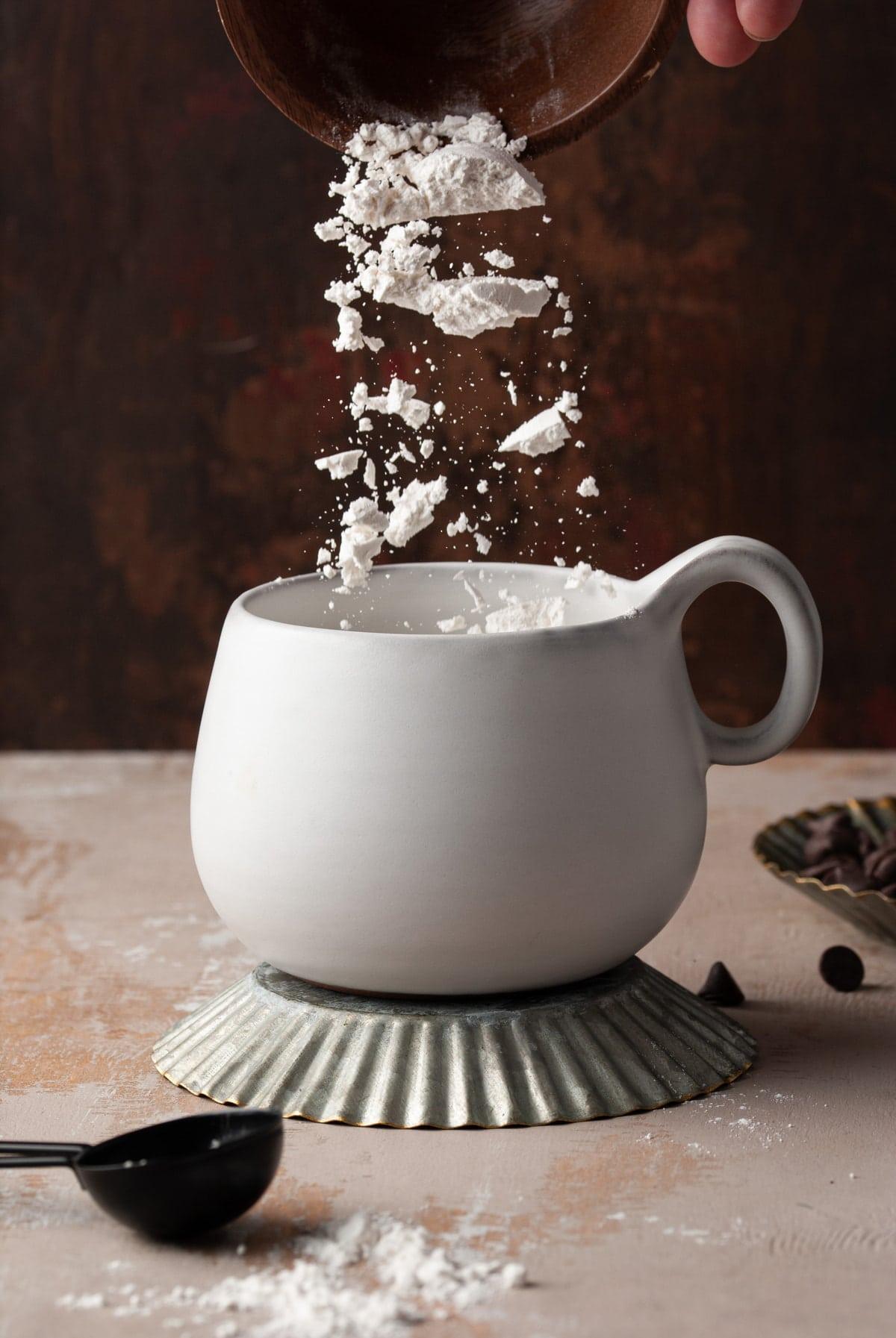 pouring flour into white mug