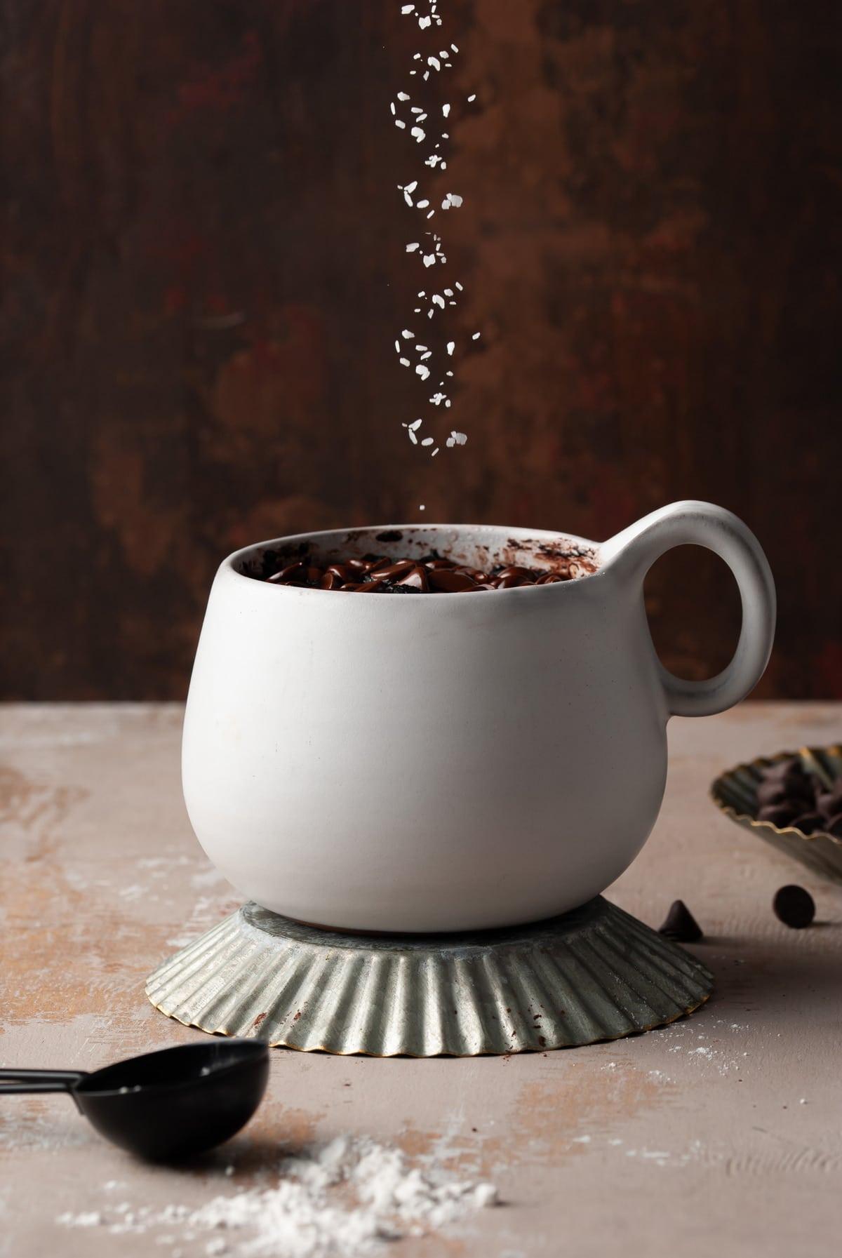 sprinkling flaky sea salt on chocolate mug dessert