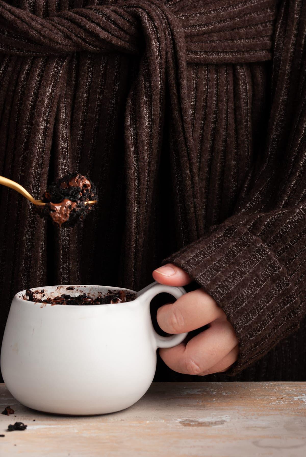 Taking a bite of vegan mug brownie on a gold spoon